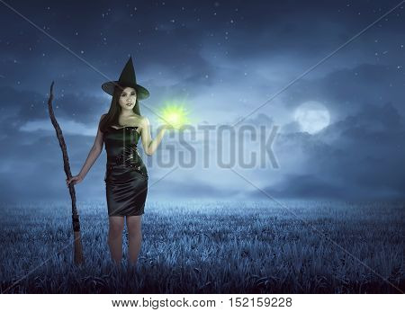 Young Asian Witch With Broom And Magic Spell