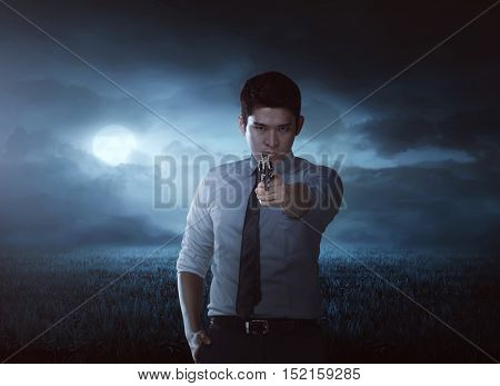 Asian man aiming gun on the meadow field