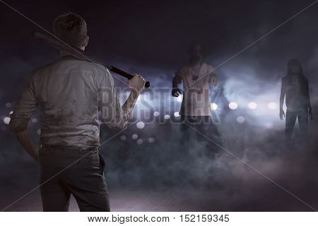 Aggressive businessman seeing zombies with a baseball bat in misty night