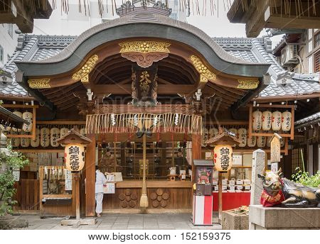Kyoto Japan - September 17 2016: Nishiki Tenman-Gu Shinto Shrine is a small wooden temple building that offers the images of the idols upfront. Gold trim gray roof paper lanterns galore and a bull statue.