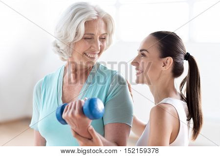 During a fitness workout. Nice positive optimistic woman holding a dumbbell and exercising while enjoying her workout with a fitness coach