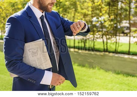 what time is it, confident man with a newspaper walking and looking on the wristwatch outdoors