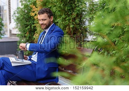 time is money, handsome businessman with coffee and newspaper looking at his watch