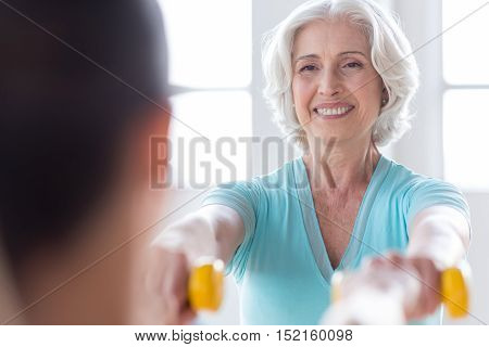 Enjoying the exercise. Pleasant delighted optimistic woman holding small rubber dumbbells in front of her and smiling while having a great time in a fitness club