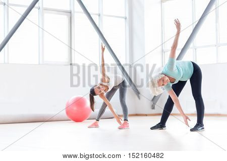 Involved in the workout. Enthusiastic joyful positive women bending forwards and raising their arms while standing near each other