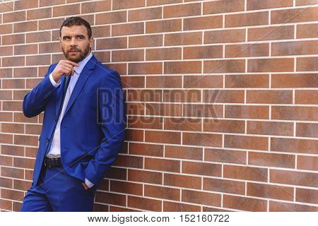 thoughtful businessman looking away while standing in front of the wall with copy space