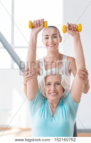 Choosing sport. Happy active confident woman raising her arms up and holding small yellow dumbbells up while working out with a fitness coach