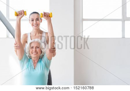 I love my job. Joyful experienced fitness coach standing behind a woman and smiling while helping her with the physical exercise