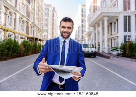 elegant smiling man walking down the street with a newspaper