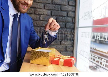 happy realtor holding keys above the gift box indoors