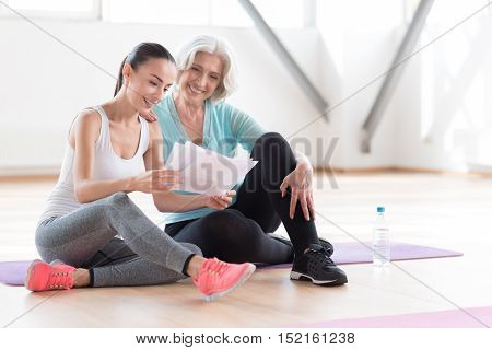 Scheme for future training. Confident happy enthusiastic woman sitting together on a yoga mat and studying the workout plan while preparing for training