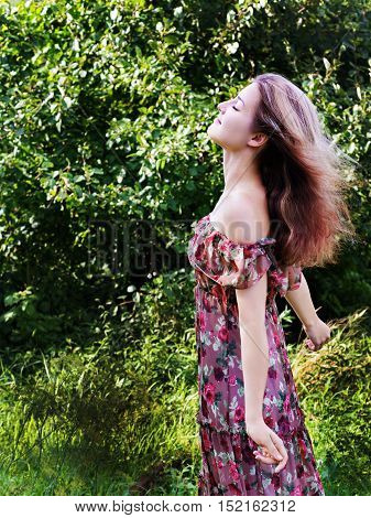 Beautiful girl in floral dress stand in garden.