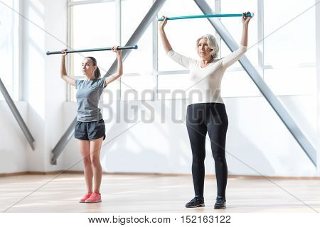 Focused on the task. Nice persistent hard working women standing together in a gym and holding their gymnastic sticks up while concentrating on the workout