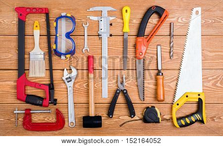 Set of various hand tools on a wooden background
