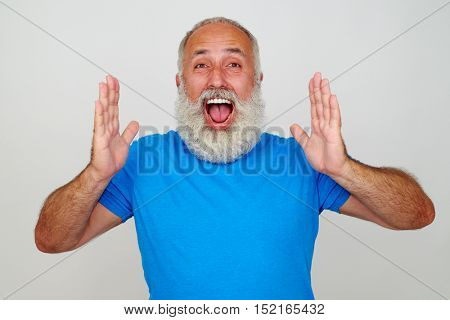 Good-looking aged man is expressing positive emotions by shouting with broad smile and happy expression on his face isolated against white background