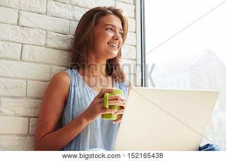 Dreaming charming girl looking through the window while sitting on the window-sill and drinking a cup of coffee