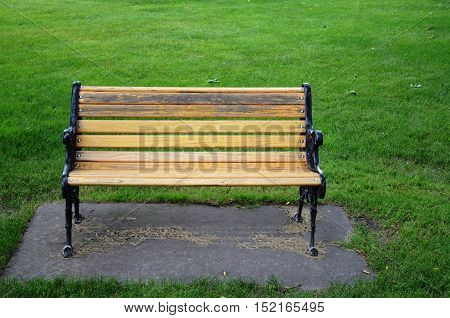 Relaxing bench for resting in the park on the green grassy lawn