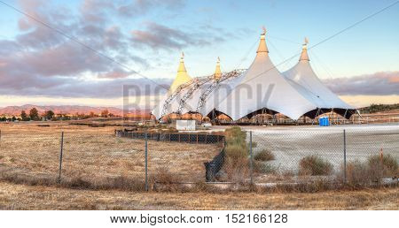 Irvine, California, USA - October 15, 2016: Sunset over a circus tent in a large field in summer.