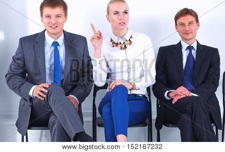 Portrait of business people sitting on chairs by office door.