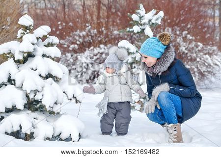 Mother and little daughter walking in deep snow in winter park. Family time. Childhood and parenthood happiness.
