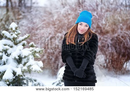 Portrait of pretty attractive girl in a fur coat and gloves in the winter park. Winter fun. Walks in the open air.