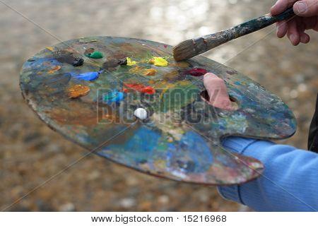 Artista maduro con paleta y pincel pintura un enfoque de paisaje costero en el cepillo.