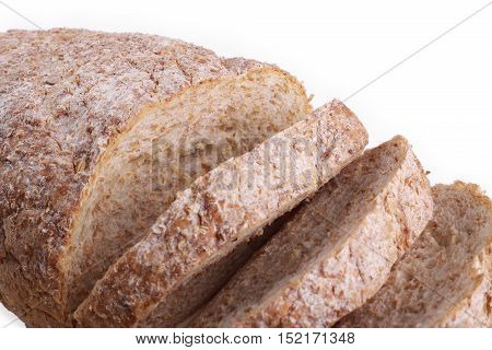 Loaf of sliced whole grain bread with flax seeds above view on white background
