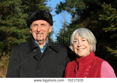 Senior couple enjoy a winter walk through a pine forest.