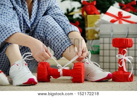 Woman In Pajamas And Athletic Shoes Unties The Bow On The Dumbbells.