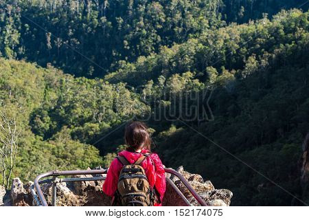 Woman At Viewing Platform Looking At Mountain Forest From Above