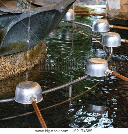 Chozuya purification fountain ladles. Traditional Japanese Shinto washbasing for ritual cleansing of worshippers at the shrine entrance. Selective focus shallow DOF. Senso-ji Asakusa Tokyo Japan