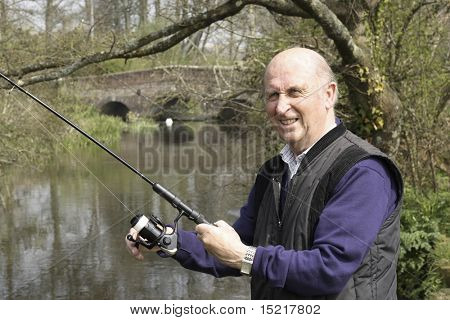 Senior man fishing by a bridge enjoying retirement.