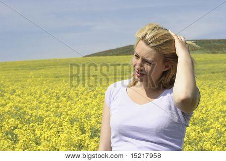 Junge Frau in einem Feld voller hell gelb Raps oder Raps.