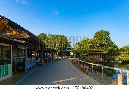 Oshino, Japan - September 2, 2016:Oshino Hakkai, Fuji Five Lakes. Japan countryside street with historic thatch roof farmhouses and pond with Mt Fuji on background