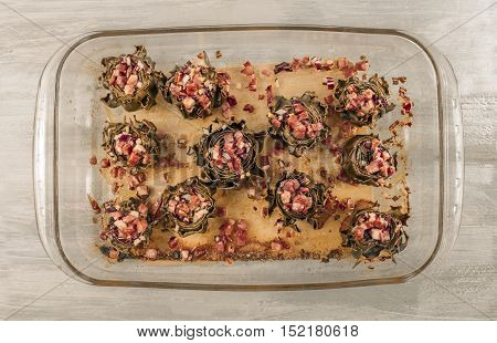 A photo of artichoke hearts cooked with jamon and red onions, a traditional Spanish meal, shot in a tray from above