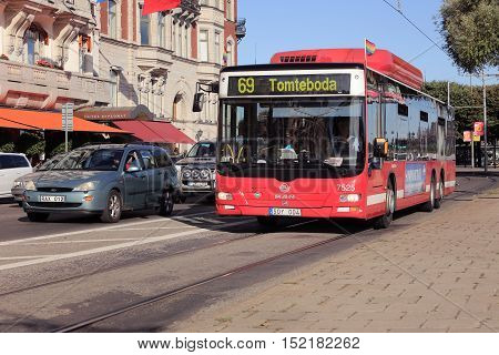 Stockholm, Sweden - August 2, 2013: A red Biogas-powered bus MAN A26 2009 model run by the Keolis Sweden AB for Storstockholms lokaltrafik SL on line 69 with destination Tomteboda onStrandvagen. The bus is decorated with rainbow flags in conjunction with