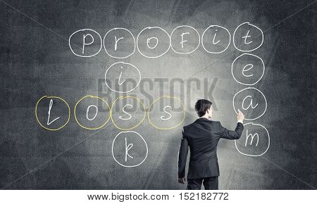 Businessman standing with back and drawing crossword for profit and loss on blackboard
