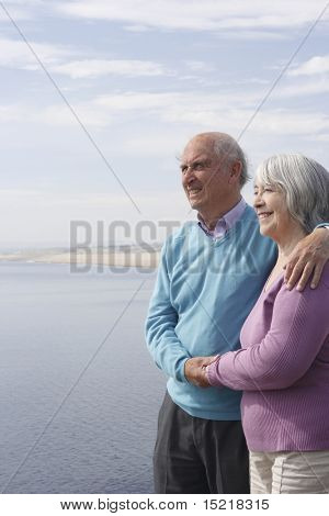 Senior couple enjoy a walk by the sea.