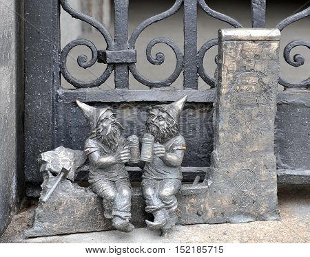 WROCLAW, POLAND - APRIL 10, 2016: Metal sculptures of dwarfs sitting and drinking beer. Wroclaw Street, Lower Silesia, Poland.