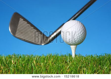 Long iron with a golf ball on a tee, grass and a blue background.