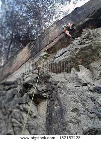 Rock climber near the top being belayed by a green rope