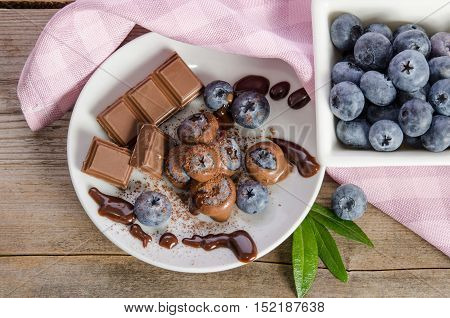 Chocolates And Cocoa Powder With Blueberries In A Porcelain Dish On Wooden Background