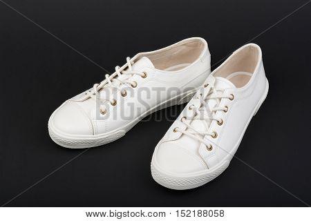 Women's white sport shoes on dark background