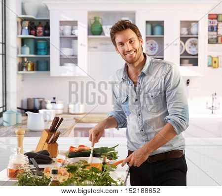 Handsome young man cooking at home in kitchen, smiling happy, looking at camera.