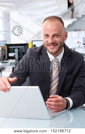 Portrait of successful happy business expert at office desk, sitting with laptop computer, smiling, looking at camera.