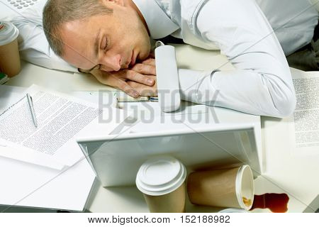 Tired businessman sleeping among papers