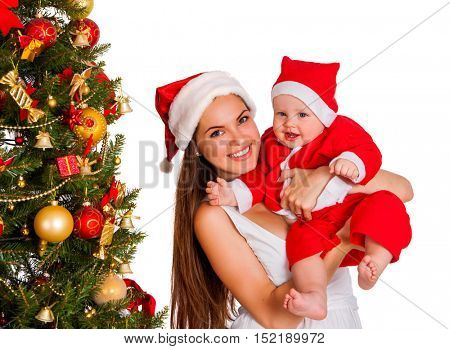 Happy mom wearing Santa hat holding baby under Christmas tree. Family concept. Isolated.