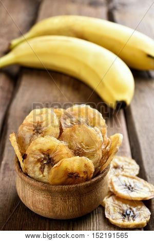 Dehydrated fruit banana chips in wooden bowl