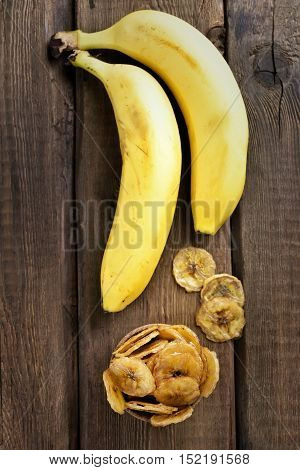 Banana chips and fresh fruits on wooden table top view