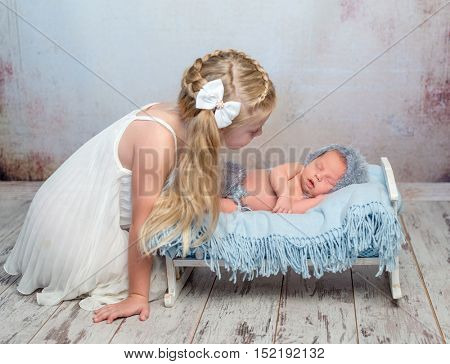 sleeping newborn boy on little bed with blue diaper and older sister watching him beside the bed